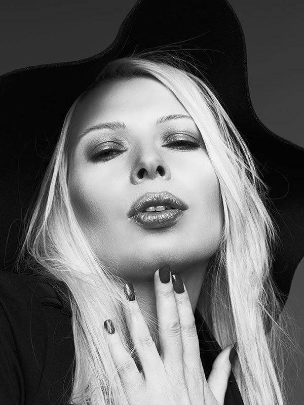 Fashionportrait, blondes Model mit langen glatten Haaren und schwarzem Wollhut