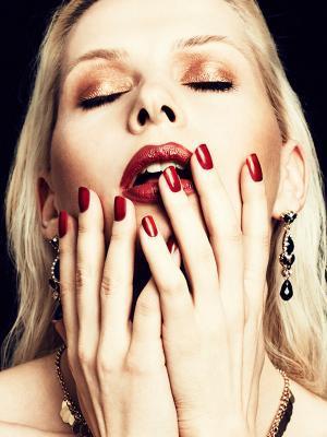 Beautybild von blondem Model mit roten Lippen und Nägeln, kupfernem Lidschatten und schwarz- goldenem Schmuck vor schwarzem Hintergrund