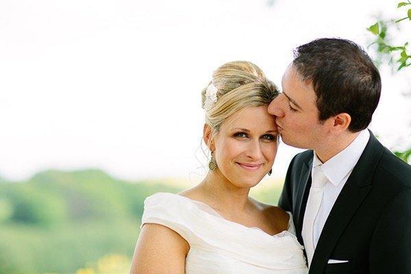 Bräutigam küsst Braut auf die Stirn, Brautmake up sehr zart, frisch und hell, Hochsteckfrisur klassisch gesteckt
