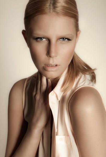Hair Styling blondes Model mit Pferdeschwanz und Mittelscheitel in beiger ärmelloser Bluse