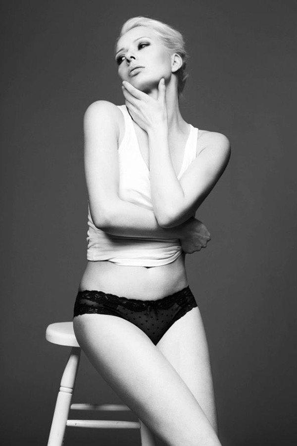 Model in sinnlicher Pose mit schlicht zusammengesteckten Haare und androgynem Style