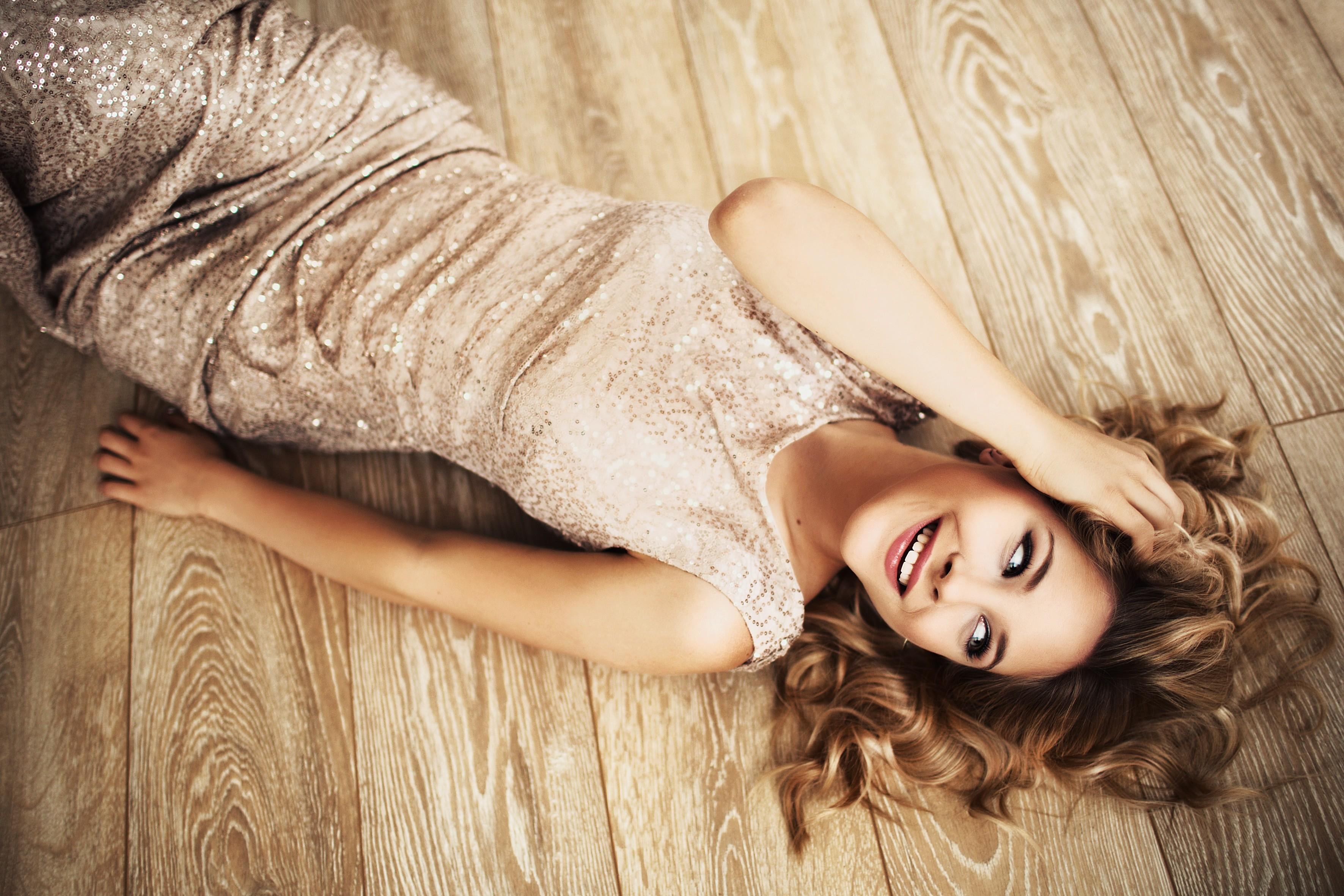 festlicher Look, Model mit natürlichen Locken auf dem Boden liegend
