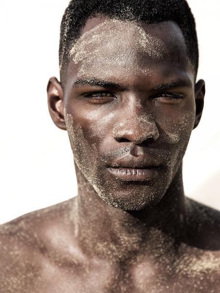 male model dunkelhäutig mit Sand im Gesicht am Strand
