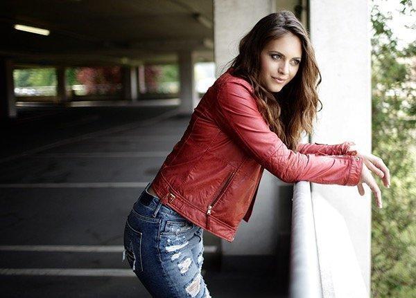 natürliche Wellen, Mädchen in zerissener Jeans und roter Lederjacke