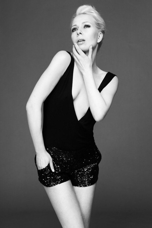 Frisur festlich und modern, blondes Model in Jumpsuit mit tiefem Dekolleté