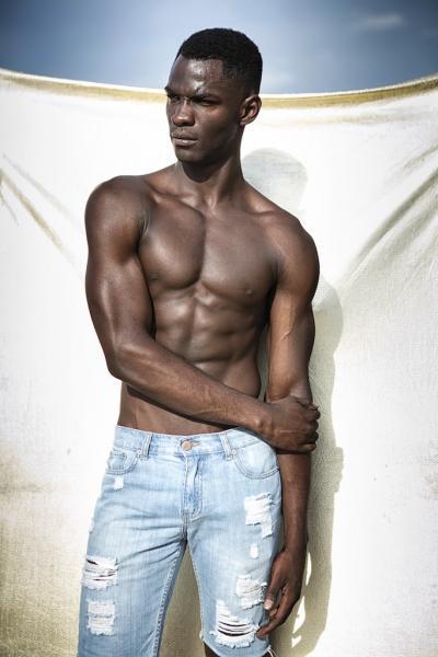 Visagistin für Outdoorproduktionen, dunkles male model mit freiem Oberkörper in heller löchriger Jeans