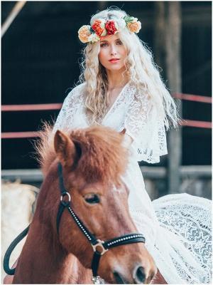 wunderschöne Boho Braut, mit Blumenkranz und langen welligen Haaren. Sie trägt ein weisses Kleid aus Spitze und reite auf einem Islandpony
