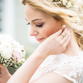 Die Brautfrisur ist ein locker zusammengenommener gelockter Pferdeschwanz, mit betontem Hinterkopf und einem Haarreif aus Blüten. Das Make up ist sehr leicht, sehr natürlich um den zarten, ebenmäßigen Sommersprossen Teint zu erhalten. Auch das Augenmaße up ist in sanften Tönen gelten, mit schön akzentuierten Augenbrauenb und einem dunklen Wimpernkranz