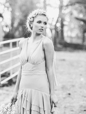 schwarz weiss Bild blondes Modell mit verträumten Blick, romantischer Flechtfrisur und Kirshcblüten im Haar