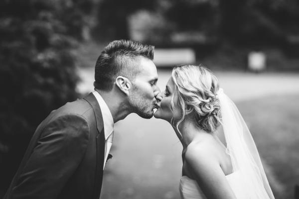Schwarz weiss Hochzeitsfoto mit sich küssendem Brautpaar, Hochzeitsfrisur, natürlich gesteckt mit locker getwistetem Nackenknoten