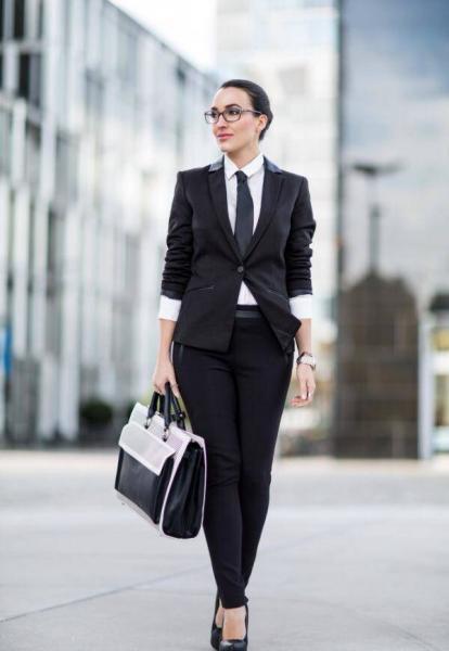 cooler, moderner Businessook, brünettes Model im stylischer femininen Anzug, und dunkler Brille