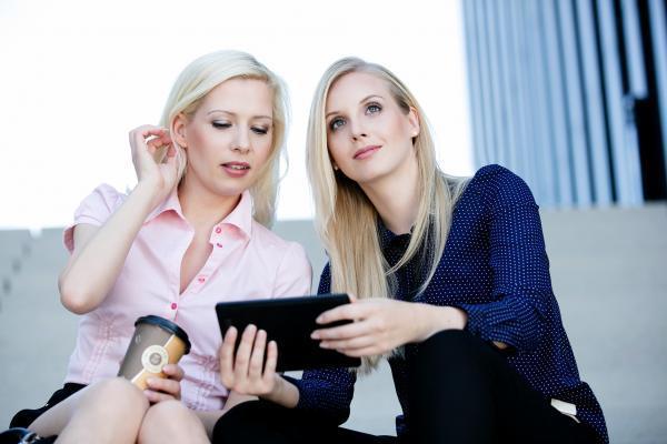business talk outdoor shooting dezentes, frisches Styling, zwei Models unterhalten sich auf der Treppe