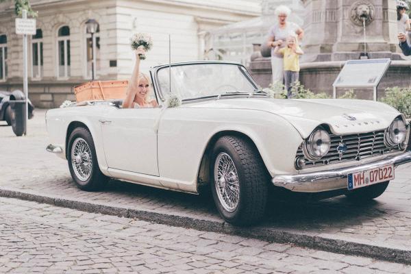 Hochzeitsauto Triumph in weiss mit romantischer Blumendekoration aus zartem Schleierkraut, perfekt für Vintage Hochzeiten