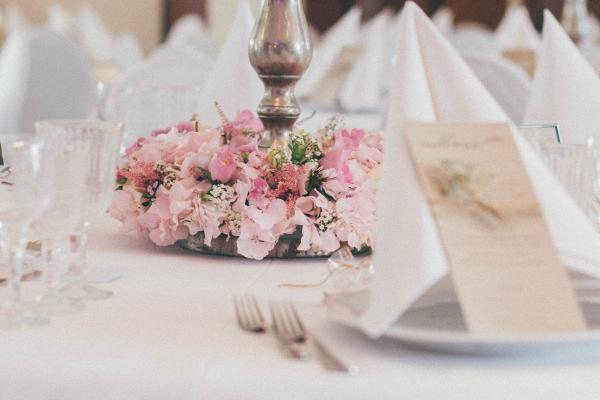 Blumendekoration für Hochzeiten nebst Hochzeitsgedeck. Zarte Farben, antike Kerzenständer und Kristallgläser machen den Vintage look aus.
