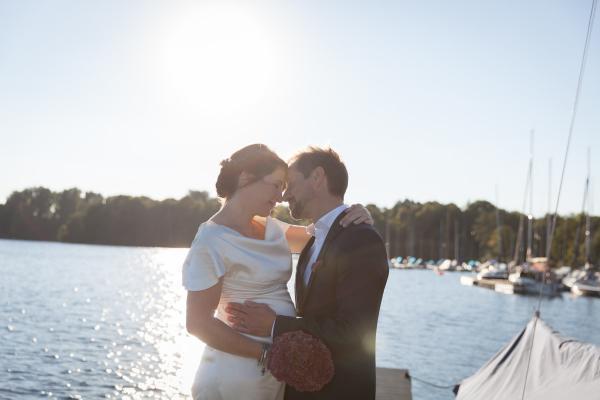 Hochzeitsbild, in wunderbarem Abendlicht, die Bratufrisur ist locker im Nacken zusammen gesteckt und das Make up ist leicht und natürlich gestaltet