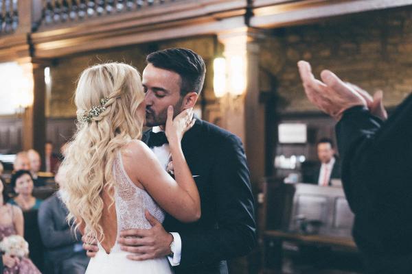 summertime wedding,natürliche, romantische Hochzeitsfrisur mit eingearbeitet feinem Kranz aus Schleierkraut und Röschen, die Location passend zur Vintagehochzeit ist rustikal, romantisch