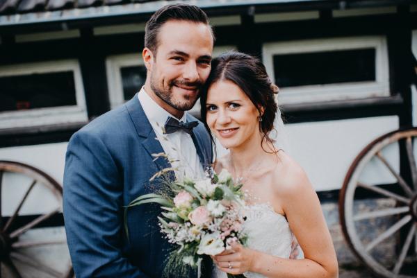 Brautpaar mit einem Strauß aus Wiesenblumen