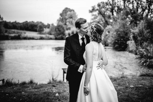 Hochzeitsfoto von einem Brautpaar am See, die Braut hat einen Bob mit leichten Wellen und einem feinem Kranz