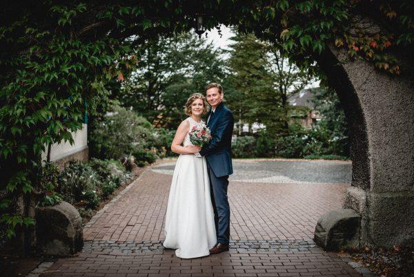 Hochzeitsfoto vom Brautpaar unter einem Torbogen