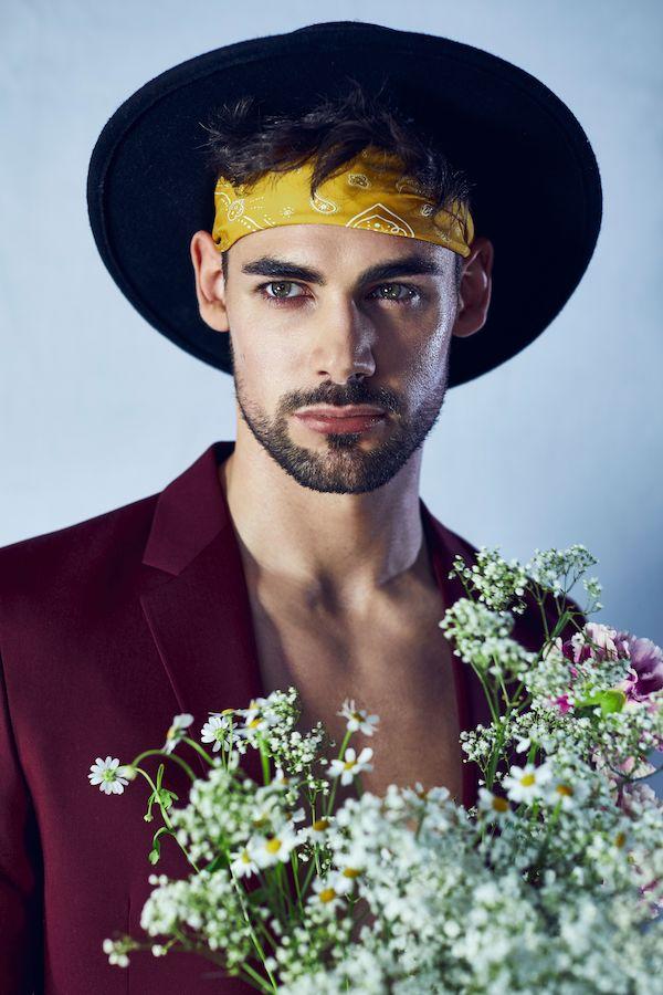 men fashion editorial, Foto von Mann mit Hut und Stirnband mit blumenstrauß