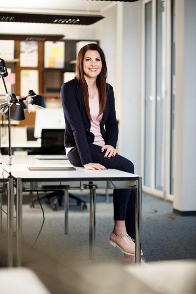 eine Frau im Anzug und dunklen langen Haaren an einem Bürotisch