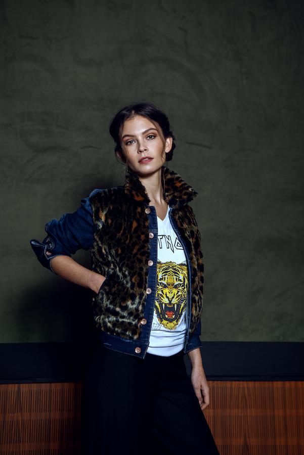 Das Modell trägt ein weisses t shirt mit Tigeraufdruck und einer Jeans-Leo Kombi Jacke