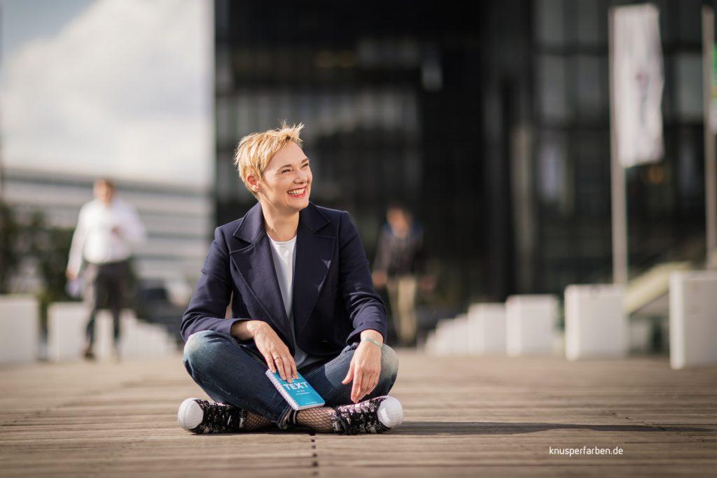 Frau im Blazer sitzend brachenspezifisch, businesstunlich geschminkt und fotografiert