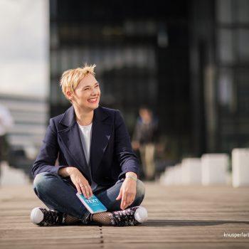individuell Business outdoor Frau im Blazer sitzend brachenspezifisch, businesstunlich geschminkt und fotografiert
