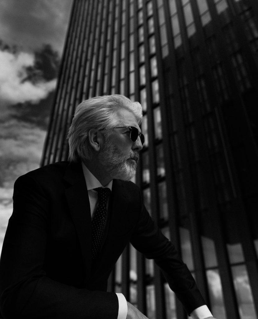 Mann mit Bart in dunklem Anzug und Krawatte mit cooler Sonnenbrille fotografiert für Brillenwerbung