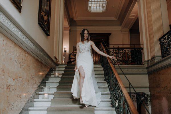 straight and naturally, First Look, sehr zart geschminkte Braut mit glattem Haar und Schleier auf der Treppe fotografiert