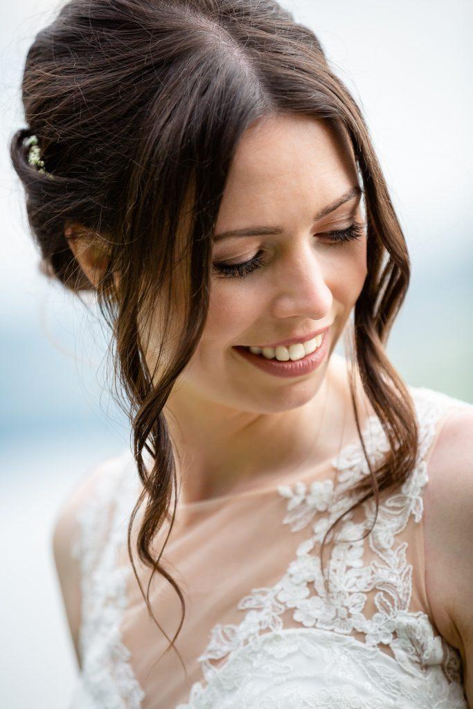 Braut mit natürlicher Hochsteckfrisur und zartem Brautmakeuup