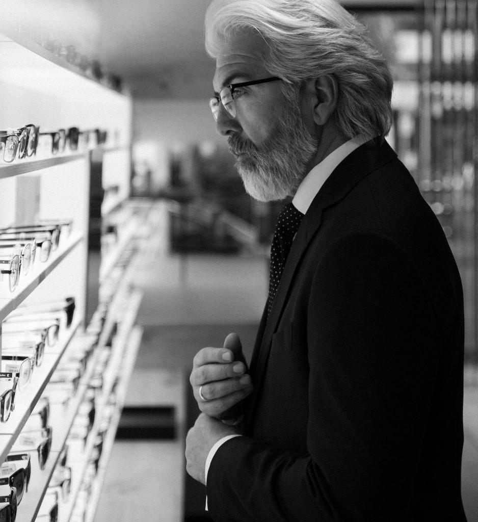 Mann mit Bart und weissen Haaren in einem Brillenladen für Brillenwerbung in schwarz weiss fotografiert