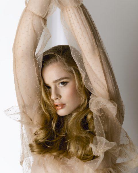 Model mit sanften Wellen und zartem Make up in nudefarbener Transporter Bluse