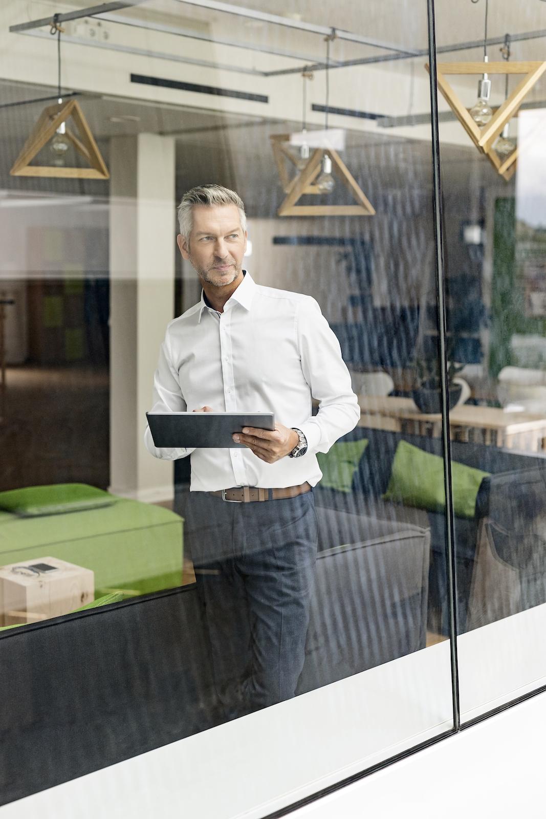 Führungskraft mit Tablet am Fenster