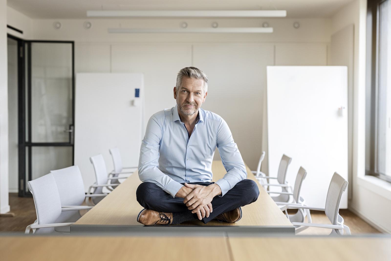 männliche Führungskraft allein auf dem Tisch sitzend in Meetingraum