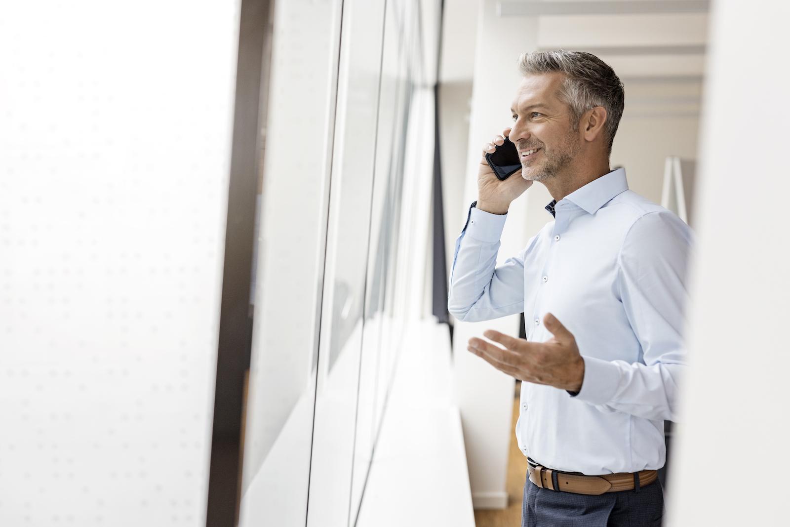 männliche Führungskraft im Büro am Fenster mit Handy