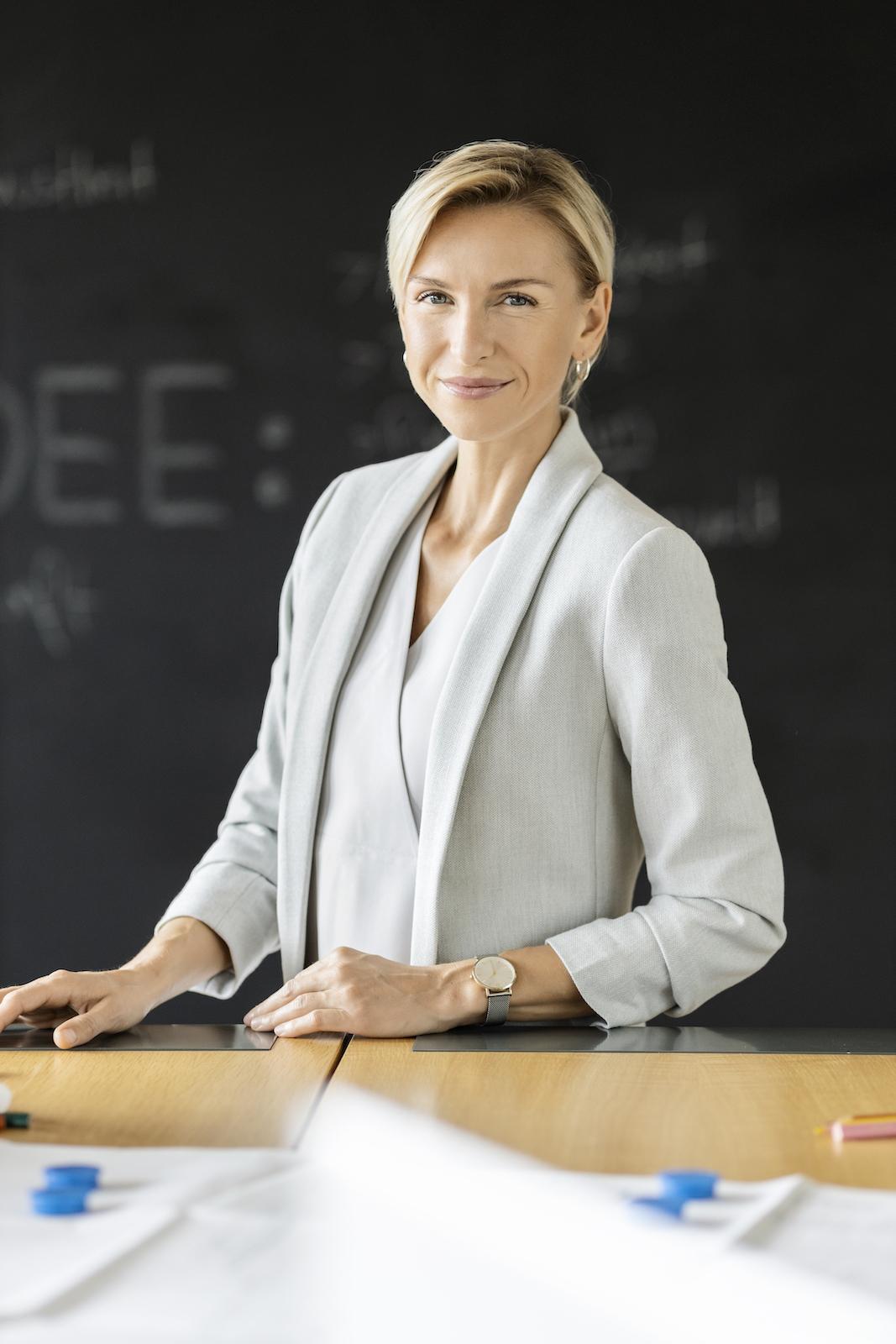 weibliche Führungskraft an Tisch mit Tafel