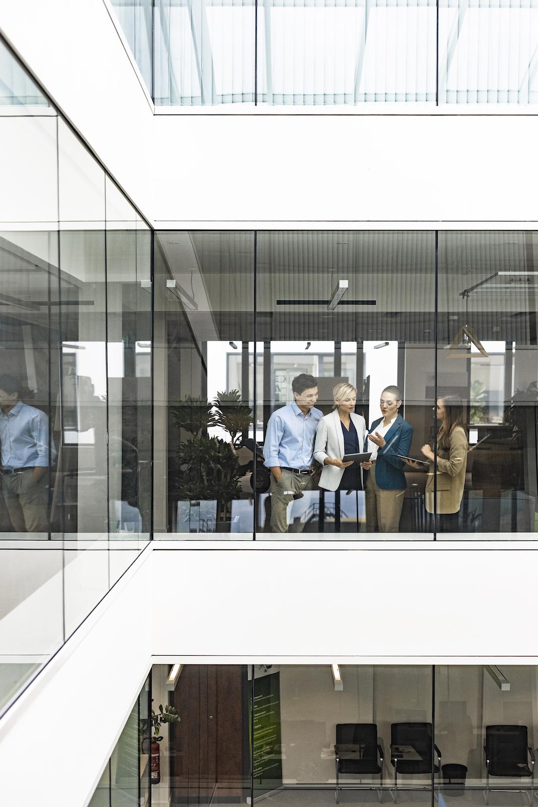 kleines spontanes Meeting an Fenster im Office mit weiblicher Führungskraft Businessstyling