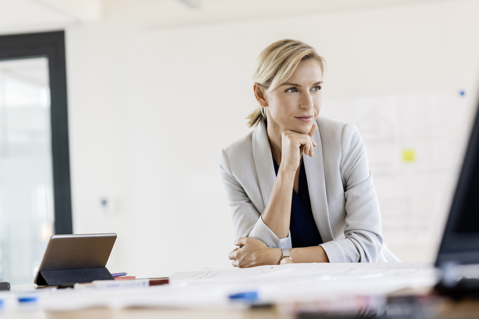 weibliche Führungskraft in grossem Büro, mit Devices am Tisch