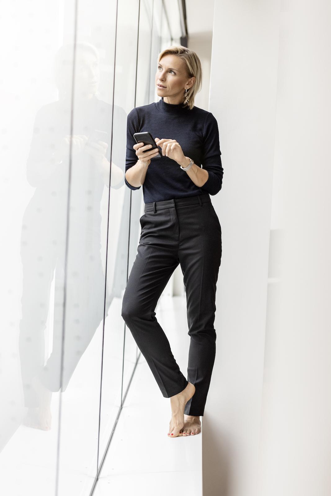 weibliche Führungskraft mit Handy im Office, barfuss und casual