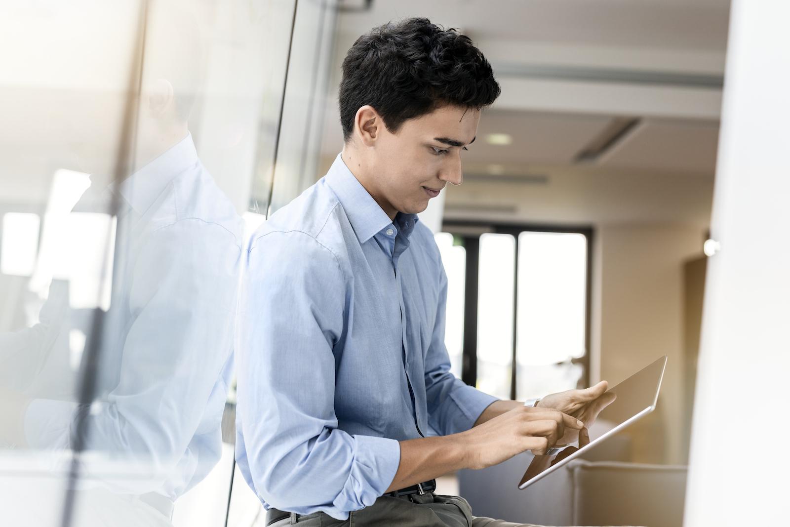 männlicher Trainee im Office mit Tablet am Fenster