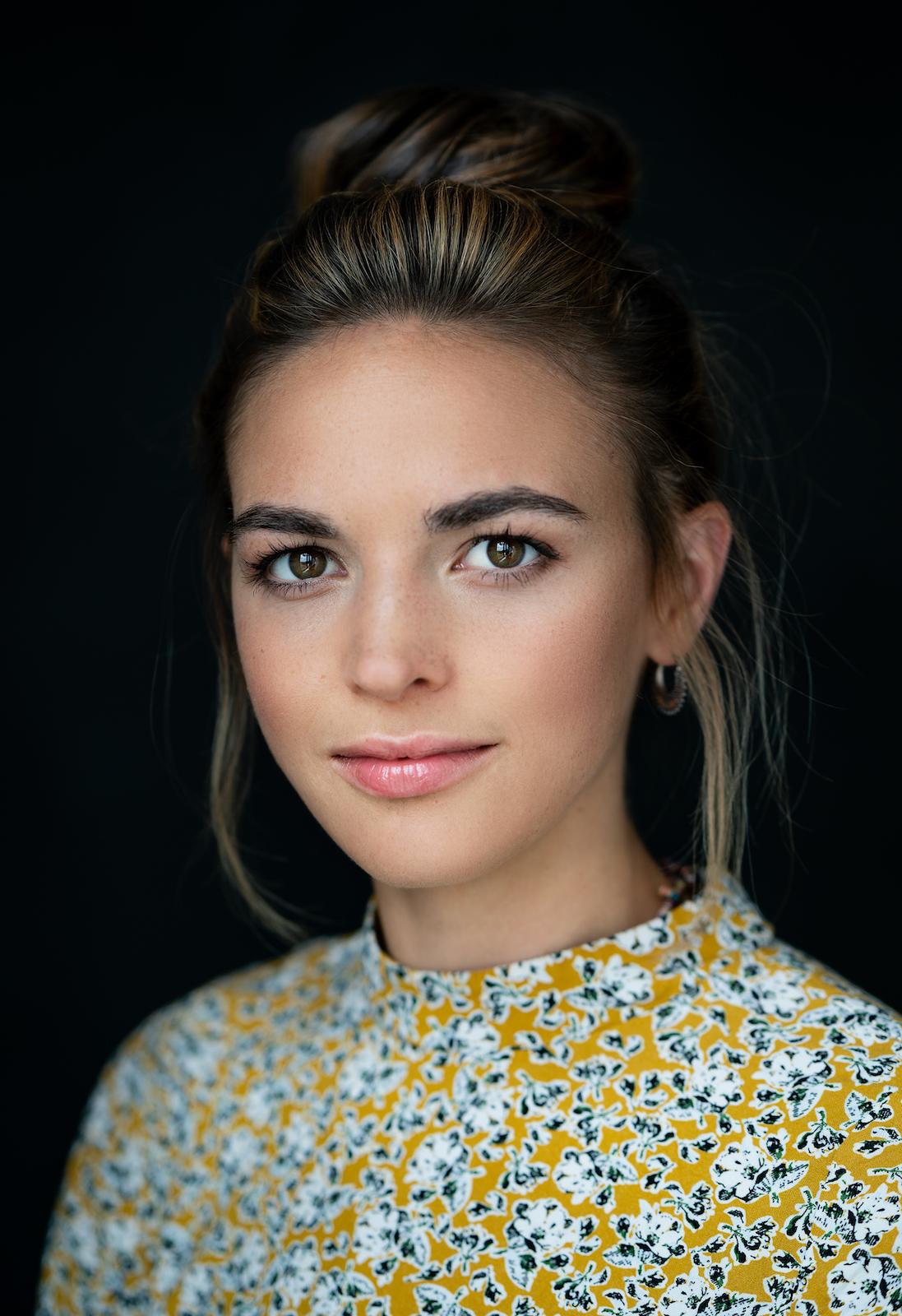modernes Business-Portrait einer jungen Frau in Blumenprint und schwarzem Hintergrund