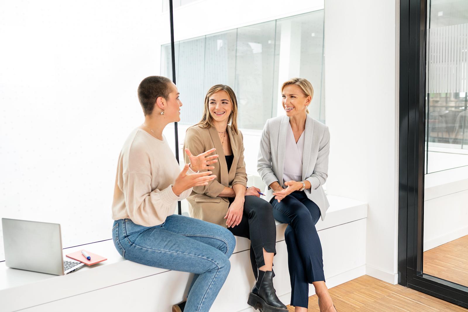 Team Gespräch dreier Frauen auf einer Fensterbank sitzend