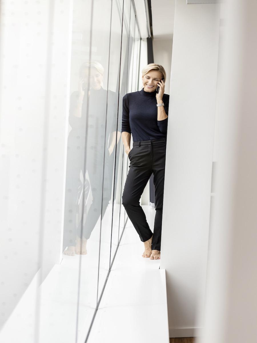 casual relaxed weibliche Führungskraft mit Handy im Office, barfuss und casual
