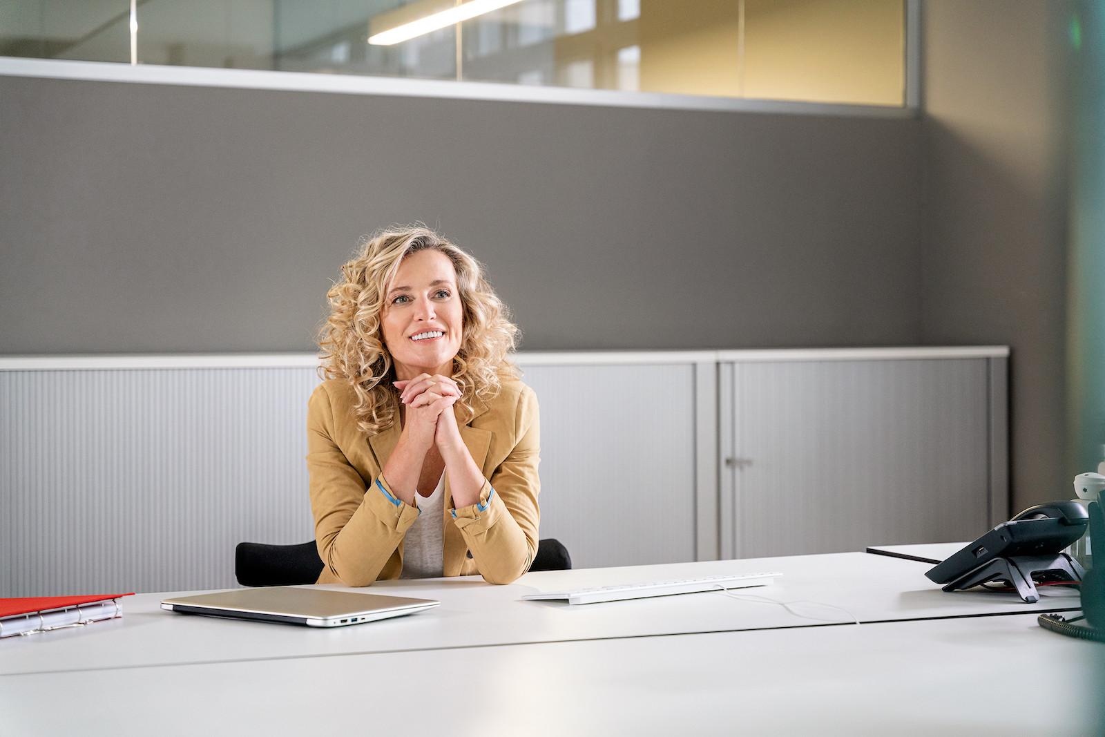 Momentaufnahme einer blonden Frau mit gelocktem Haar im Büro