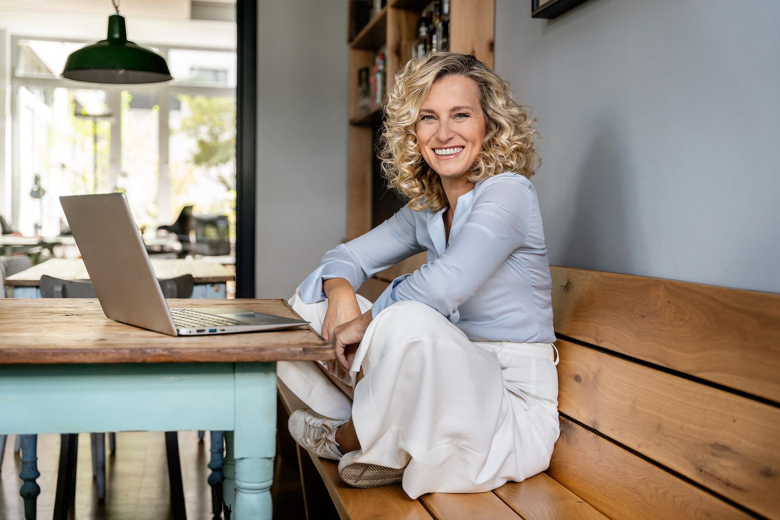 legere Business Aufnahme, Frau mit lockigem Haar im Schneidersitz