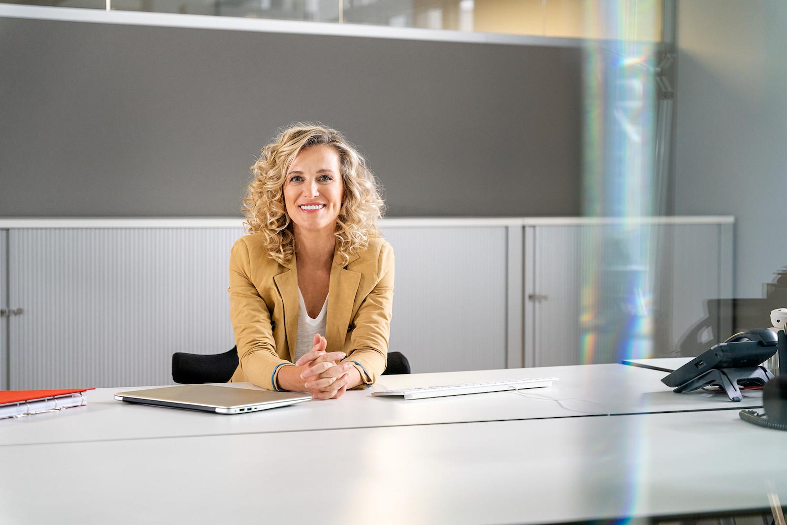 Cleanes Business Bild einer blonden Frau mit lockigem Haar